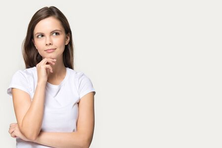Pensive millennial girl isolated on grey studio background thinking looking at blank copy space aside, thoughtful young woman touch chin pondering over sale offer, consider promotion or deal