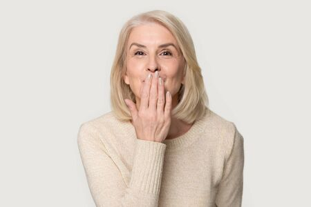 Happy positive aged Caucasian woman in sweater isolated on grey studio background look at camera send blow air kiss, beautiful smiling senior female show love affection touch hand lip salute Zdjęcie Seryjne