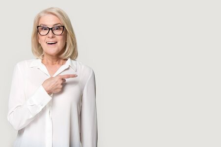 Surprised mature lady wearing glasses blouse isolated on grey studio background point at blank copy space aside, senior woman in spectacles feel shocked by amazing good promotion, sale offer or deal Фото со стока