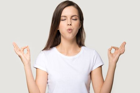 Peaceful young woman isolated on grey studio background meditating with mudra hands, calm millennial girl practice yoga with eyes closed, breathing deep, controlling emotions. Stress free concept Banco de Imagens