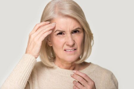 Unwell mature aged woman isolated on grey studio background touch head suffer from migraine or headache, frustrated senior lady having blurry eyes or dizziness. Health problem, ophthalmology concept