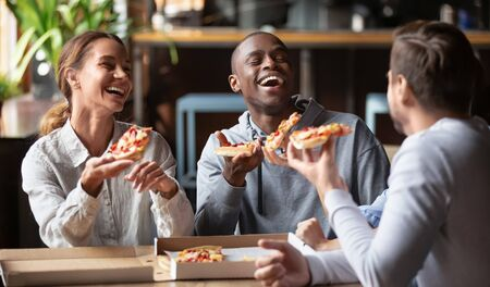 Joyful multicultural friends laughing sharing takeaway meal together, happy diverse young people group holding slices in cafe indoors, multi ethnic students eating pizza sit at table at party meeting Stockfoto