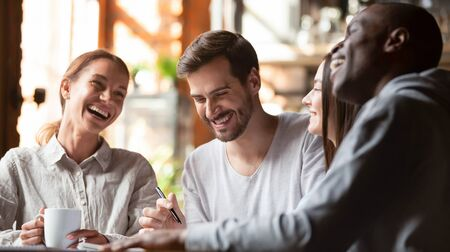 Happy multiracial young friends relax together talking laughing sit at cafe table, cheerful diverse students girls and guys people group studying having fun indoor, multicultural friendship concept