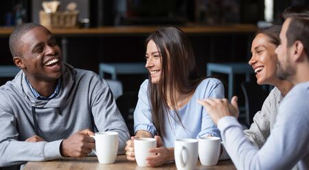 Multiracial friends girls and guys having fun laughing drinking coffee tea in coffeehouse, happy diverse young people talking joking sitting together at cafe table, multicultural friendship concept Stockfoto