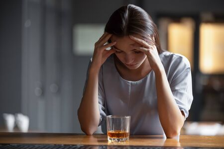 Depressed sad young addicted woman feeling bad drinking whiskey alone in bar, stressed frustrated lonely female drinker alcoholic suffer from alcohol addiction having problem, alcoholism concept