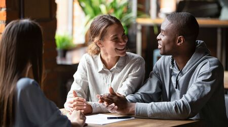 Smiling young mixed ethnicity couple talk decide on financial mortgage deal consider insurance loan meeting bank manager, female insurer consult interracial customers offer contract, business advice