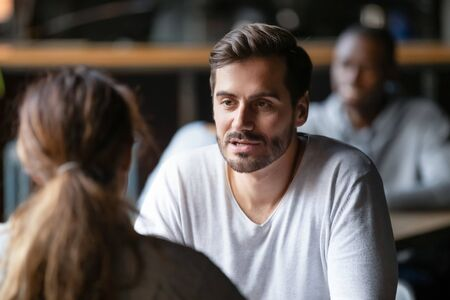 Young serious man having conversation with woman girlfriend sit at cafe table, focused male friend talking to female colleague client solving problem discuss work issues at meeting in coffeehouse Stockfoto