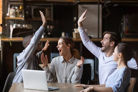 Excited diverse friends celebrate online win watch football game on laptop sit at cafe table together, overjoyed multicultural young football fans supporters happy with victory goal score at party Stock Photo