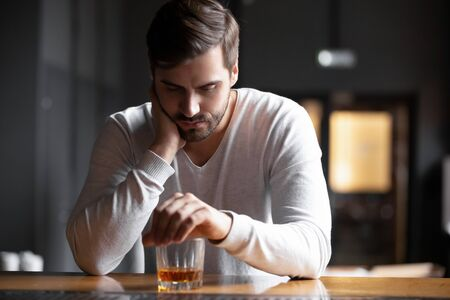 Upset young man drinker alcoholic sitting at bar counter with glass drinking whiskey alone, sad depressed addicted drunk guy having problem suffer from alcohol addiction abuse, alcoholism concept Stock Photo