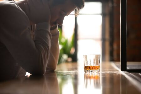 Depressed sad drunk addicted man in trouble sitting at bar counter drink whiskey alone feeling pain hangover lonely hopeless, stressed upset drinker guy having problem alcohol addiction abuse concept
