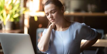 Stressed upset business woman feeling backpain working on laptop sitting in incorrect posture, tired fatigued student rub back suffer from spine muscular pain injury lumbar backache concept in office