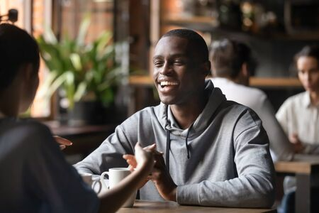 Happy young black man talk to female friend girlfriend on romantic date sit at cafe table, smiling millennial african guy having pleasant conversation flirt with white woman at meeting in coffeeshop