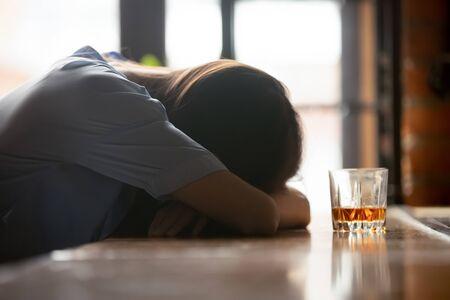 Donna ubriaca ubriaca che dorme sul bancone del bar vicino al bicchiere di whisky al mattino, alcolizzata forte bevitrice svenuta sdraiata addormentata dopo l'alcol, problema di alcolismo, concetto di dipendenza da alcol Archivio Fotografico