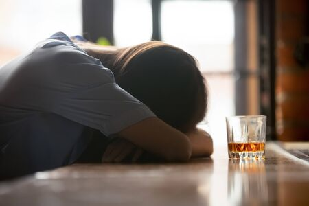 Drunk intoxicated woman sleeping on bar counter near whiskey glass in the morning, female heavy drinker alcoholic passed out lying asleep after booze, alcoholism problem, alcohol addiction concept