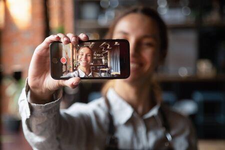 Feliz joven camarera vlogger sosteniendo un blog de video de grabación de teléfono inteligente en la pantalla móvil, sonriendo a la chica del blogger del trabajador de la cafetería del propietario del café milenario vistiendo delantal disparando vlog mirando a la cámara del teléfono Foto de archivo