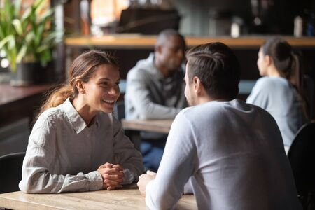 Happy young couple chatting sit at cafe table, smiling woman talking to man boyfriend at date in restaurant, millennial girl having conversation flirt with male friend in coffee shop at meeting