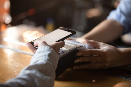 Woman customer holding phone near nfc terminal make contactless mobile payment using app concept in store restaurant, female buyer client pay with cellphone via pos machine on counter, close up view