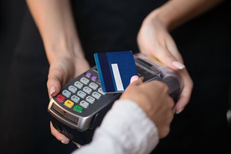 Female customer pay hold credit card use contactless nfc technology concept, woman consumer make transaction payment on wireless terminal rfid pos reader machine in restaurant store, close up view
