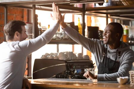 Happy african american barista wearing apron giving high five to caucasian customer stand at counter in coffee shop, smiling friendly male black waiter cafe owner greeting white client in coffeehouse Stockfoto