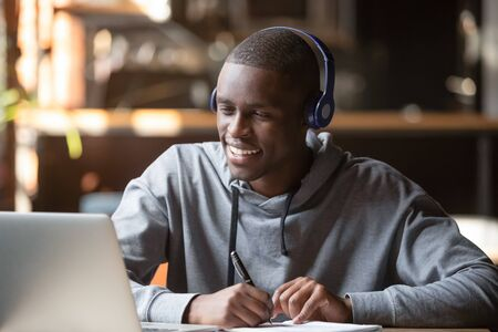 Smiling african young man student wear headphones looking at laptop screen writing notes, happy black guy e-learning in internet study online with skype teacher on computer watch webinar sit in cafe