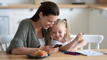 Woman sit at table hold phone daughter distracted from drawing with felt-tip pens on exercise book look with mom at smartphone screen, watching video have fun online use apps enjoy free time concept