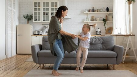 Active family fooling around in cozy light living room, young mother holding hands little preschool cheerful daughter people enjoy music dancing at home, leisure activity, weekend, free time concept