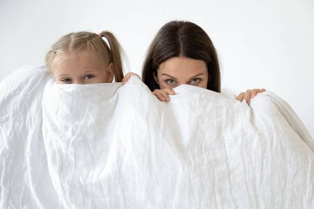 Little daughter young mother european family peeking looking at camera hiding behind white blanket standing against grey wall, empty space on duvet for advertisement quality bed clothes store concept