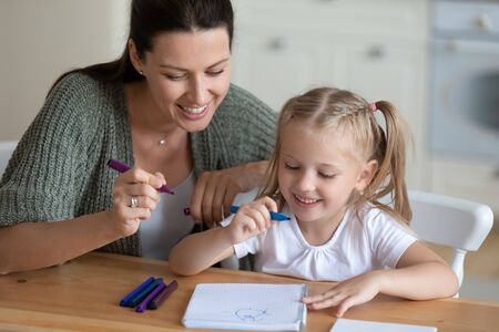 Loving mother and daughter sitting at table having good free time drawing together with colorful felt-tip pens on exercise book, parent helping to child with picture hobby and leisure activity concept Imagens