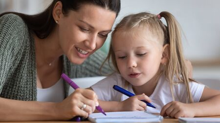 Painstaking preschool daughter and mother sitting at table draw together with felt-tip pens on exercise book close up image. Pastime and hobby, educational learning process development of kid concept