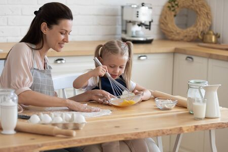 Little girl holding whisk stirring eggs in bowl making with mommy mixture for morning pancakes, mother daughter preparing sweet pie using flour sugar milk sitting on chairs at table in modern kitchen