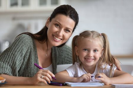 Beautiful woman and little adorable daughter sitting at table at home drawing with felt-tip pens looking at camera, concept of hobby of children, motor skills improvement, develop child s creativity Stock fotó
