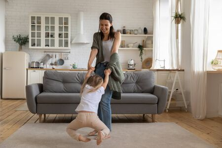Beautiful woman spinning in circle hold hands little daughter standing in living room, nanny spend day with small girl at home, leisure activity active lifestyle, priceless time with offspring concept 写真素材