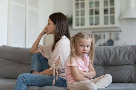 Fille boudeuse mère insatisfaite assise sur un canapé regardant de différents côtés, conflits familiaux, incompréhension et fossé générationnel, les femmes plus âgées et plus jeunes ne se comprennent pas le concept Banque d'images