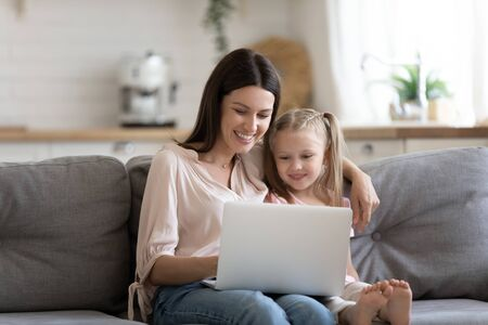 Young mother and preschooler daughter sitting on couch at home, parent teach little kid girl how to use device application, watching amusing cartoons or online educational program in internet concept