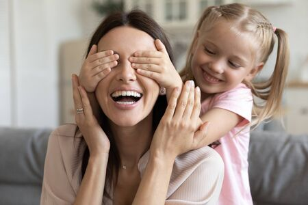 Close up view preschool daughter closes her mother eyes with hands play together have fun spend funny leisure at home, loving kid girl prepare surprise for beautiful mom showing care and love concept Banco de Imagens