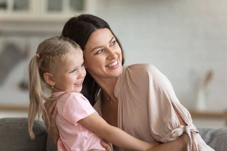 Beautiful european mother embraces little sweet daughter people sitting on couch looking out the window at home, mom touch kid girl showing protection and endlessly love, happy family portrait concept