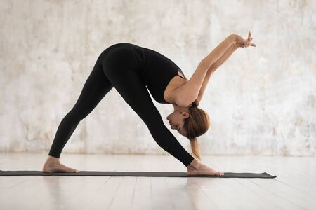 Attractive young woman wearing black sportswear practicing yoga, standing in Parsvottanasana pose on mat, Pyramid exercise, beautiful girl working out at home or in yoga studio with grey walls