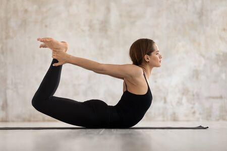 Beautiful young woman wearing black sportswear practicing yoga, doing Dhanurasana exercise, Bow pose, attractive sporty girl working out at home or in yoga studio with grey walls side view