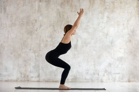 Beautiful young woman wearing black sportswear practicing yoga, doing Chair exercise, standing in Utkatasana pose side view, sporty girl working out at home or in yoga studio with grey walls