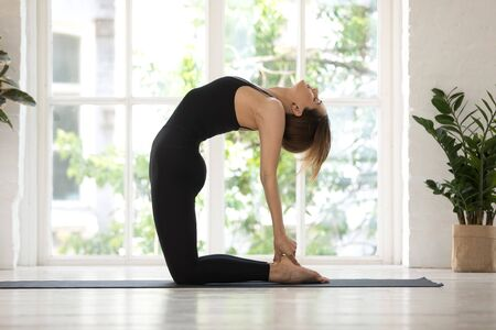 Beautiful woman standing in Camel pose on mat, doing Ustrasana exercise, practicing yoga, sporty girl wearing black sportswear working out at home or in yoga studio with big window and plants