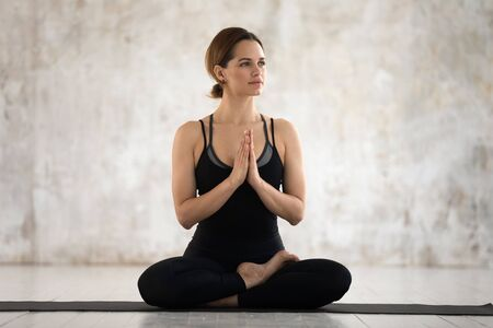 Calm young woman wearing black sportswear practicing yoga, doing Padmasana exercise, sitting in Lotus pose on mat, namaste hands, girl working out at home or in yoga studio with grey walls Stock fotó