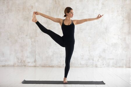 Beautiful woman wearing black sportswear practicing yoga, doing Extended Hand to Big Toe exercise, standing in Utthita Hasta Padangustasana pose, working out at home or in yoga studio with grey walls 写真素材