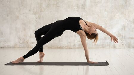 Young woman wearing black sportswear practicing yoga, standing in Wild Thing pose, attractive sporty girl doing Camatkarasana exercise, working out at home or in yoga studio, horizontal banner Stockfoto