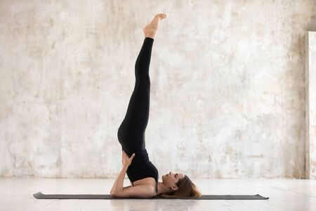 Beautiful woman wearing black sportswear practicing yoga, standing in Salamba Sarvangasana pose, doing Shoulder stand exercise, sporty girl working out at home or in yoga studio with grey walls