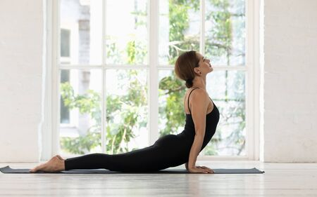 Beautiful woman wearing black sportswear practicing yoga, stretching in Cobra pose on mat, doing Bhujangasana exercise, sporty girl working out at home or in yoga studio with big window