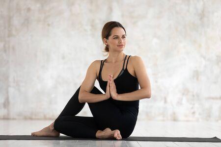 Belle femme portant des vêtements de sport noirs, un pantalon pratiquant le yoga, assise dans la pose d'Ardha Matsyendrasana avec namaste, faisant de l'exercice Half Lord of the Fishes, une fille travaillant à la maison ou dans un studio de yoga Banque d'images