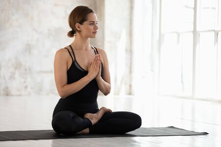 Calm young woman wearing black sportswear practicing yoga, doing Padmasana exercise, sitting in Lotus pose on mat, stress relief, namaste hands, girl working out in yoga studio with big windows Stock Photo