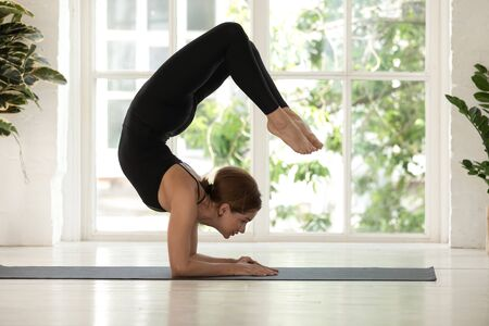Young woman standing in Scorpion pose, doing vrischikasana exercise, practicing yoga, attractive girl wearing black sportswear working out at home or in yoga studio with big window and plants