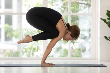 Young woman wearing black sportswear doing Bakasana exercise, standing in Crane pose, practicing yoga on mat, beautiful sporty girl working out at home or in yoga studio with big window