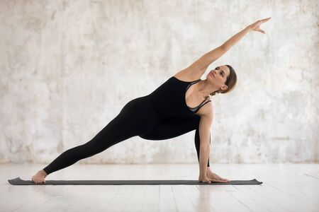 Beautiful woman wearing black sportswear practicing yoga, doing Utthita parsvakonasana exercise, standing in Extended Side Angle pose, girl working out at home or in yoga studio with grey walls